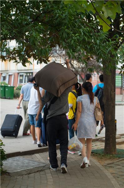爸爸用肩头为子女扛起重重的行李