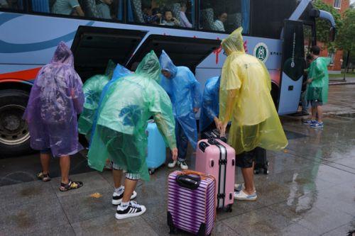 学生会成员们冒雨帮助新生搬运行李