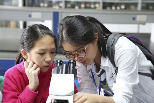 志愿者在帮助小朋友调整显微镜