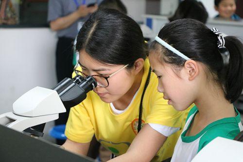 志愿者在协助小朋友使用显微镜