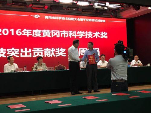 黄冈市市委书记刘雪荣为黄刚弄科技突出贡献奖获得者、我校校友周强颁发证书