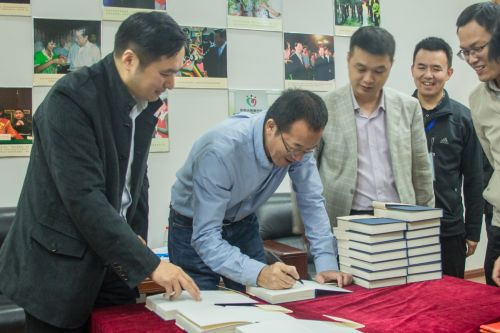 俞敏洪参观本禹志愿服务队活动室并在书籍上签名留念(学通社记者 李晔 摄)