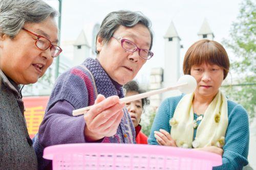 夹乒乓球比赛,参赛者正用筷子将乒乓球夹入篮子中,规定时间内数量多者获胜(学通社记者 蒲振 摄)