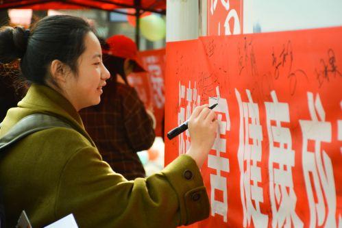 """一名同学在""""e路阳光""""的横幅上签上自己的名字 (学通社记者 蒲振 摄)"""