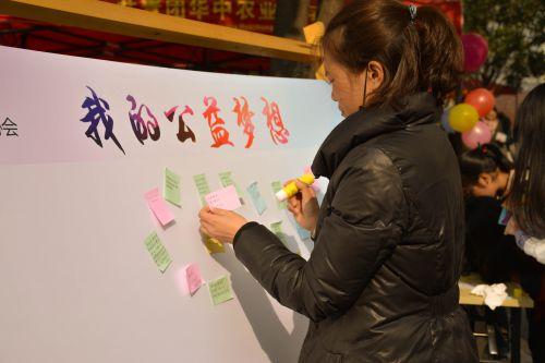一位同学在展板上贴上自己的公益梦 (学通社记者 蒲振 摄)