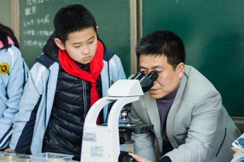 陈大松老师为同学们调试显微镜进行观察(学通社记者 彭雨格 摄)