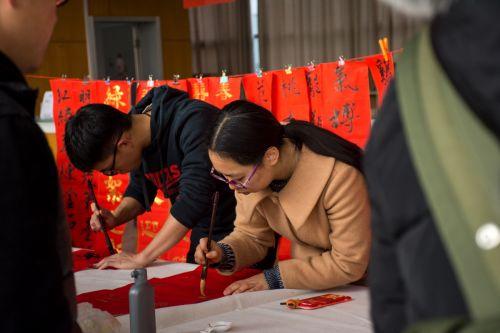 书法协会的成员专心致志书写对联 学通社记者赵婉玥摄