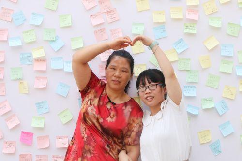 """与母亲""""比心""""(学通社记者 吴毅博摄)"""