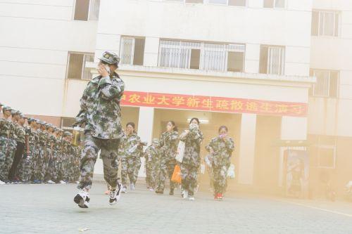 2018新生消防安全演习,火情警报后,参与演习的同学从着火楼栋里以湿毛巾掩鼻跑出(学通社记者 彭韵菲 摄)