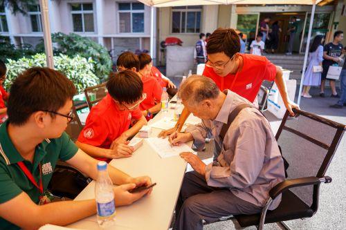 10月1日下午工学院签到处,一位退休教师在签到的同时,与学生志愿者交谈【学通社记者 李烨 摄】