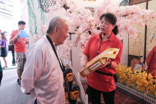 服务人员向老校友介绍新推出的水稻【学通社记者 吴毅博摄】