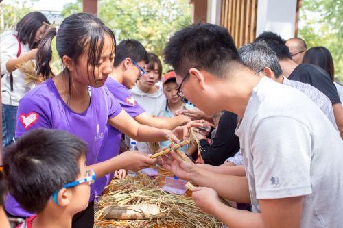二十四节气柱旁,志愿者指导校友制作稻草人 学通社记者 伍儆人 摄