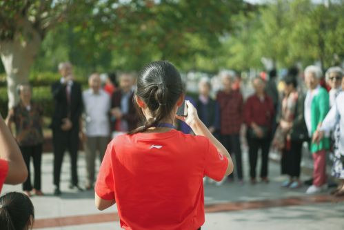 十月二号上午体育馆签到处志愿者为校友拍摄合影【学通社记者李烨摄】