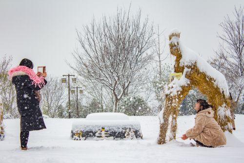 两位同学在雪中的稻草人前拍照留念【学通社记者 罗腾 摄】