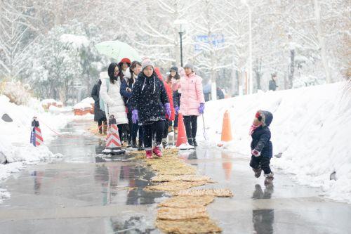 人们走在铺设了防滑竹垫的路上【学通社记者 周奕淳 摄】