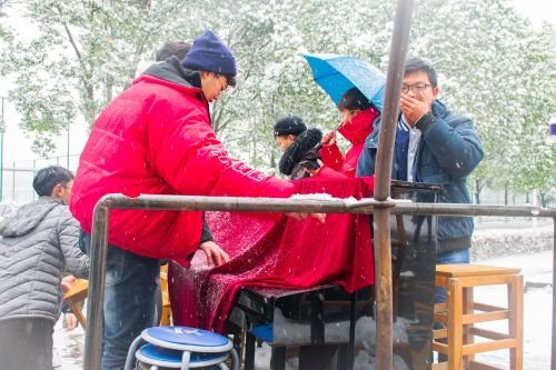 校艺术团的工作人员在雪中运送跨年所需要的设备【学通社记者 刘航 摄】