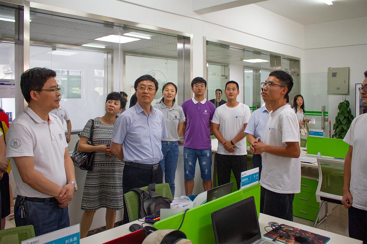 专家在观看双水双绿小龙虾创业组的获奖墙【学通社记者 李靖威 摄】