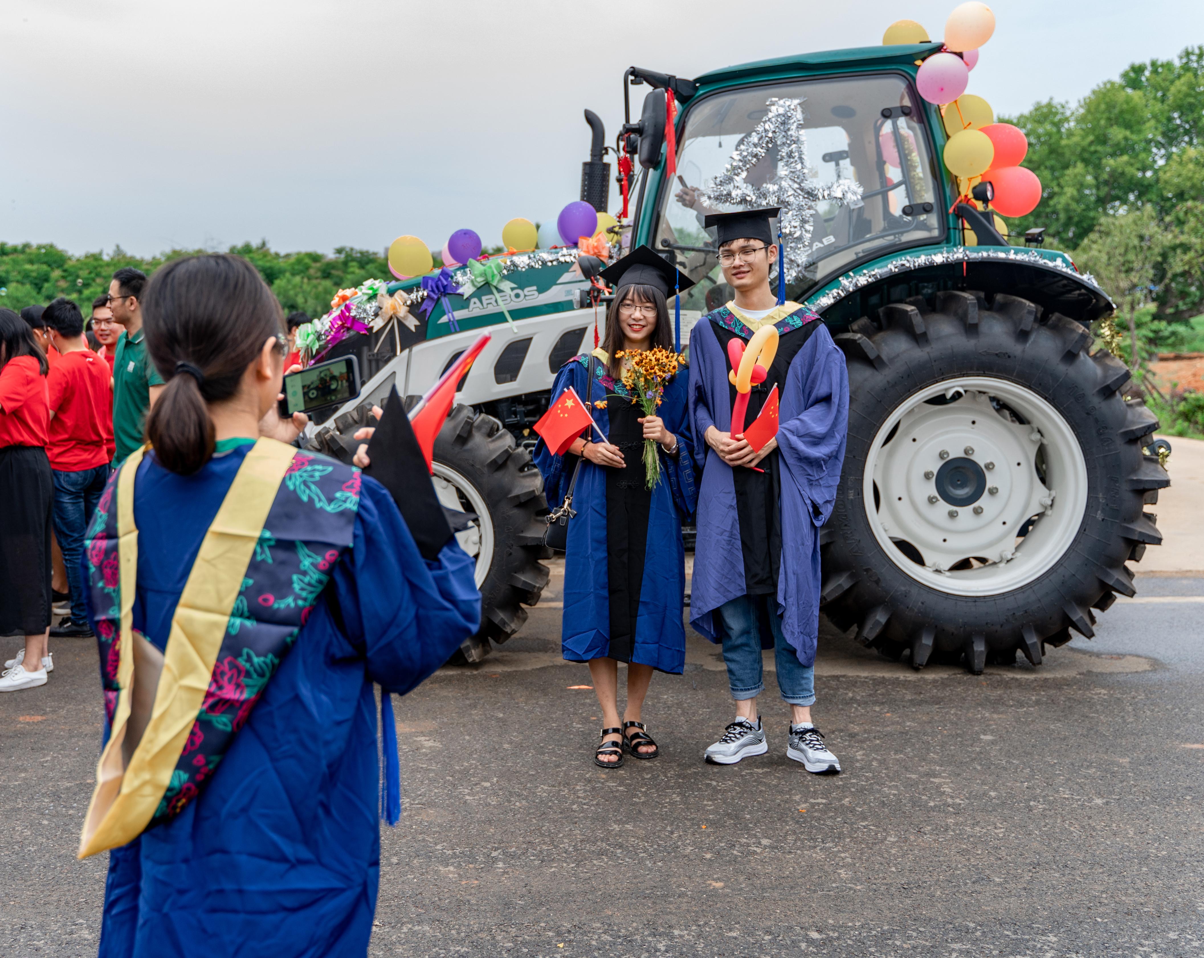 毕业生穿着学士服在拖拉机前拍照【学通社记者 罗腾 摄】