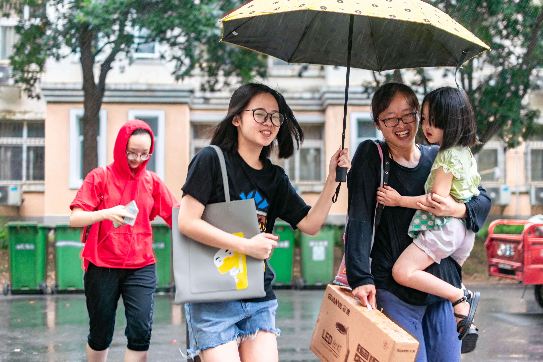 一位新生和家长冒雨进入寝室【学通社记者 刘航 摄】