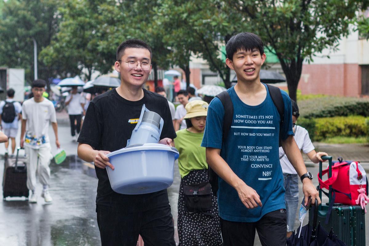 志愿者陪同新生买完生活用品后在路上有说有笑【学通社记者 肖倩摄】