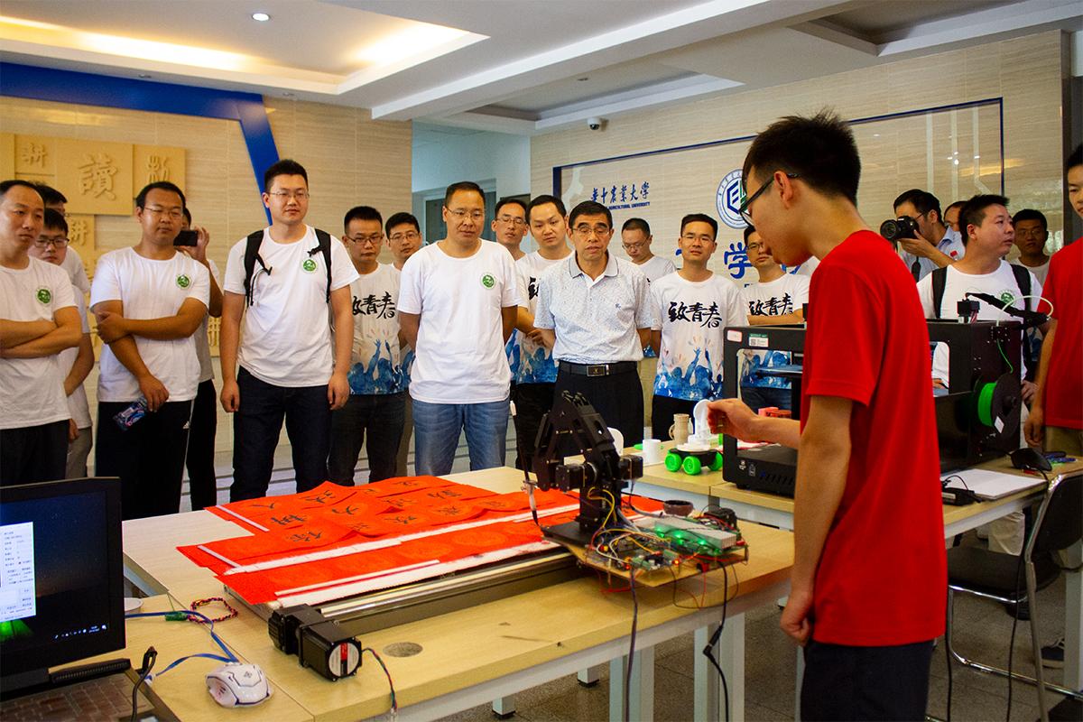 校友们在听17级的学术介绍学科体验活动所展示的机器【学通社记者 李靖威 摄】