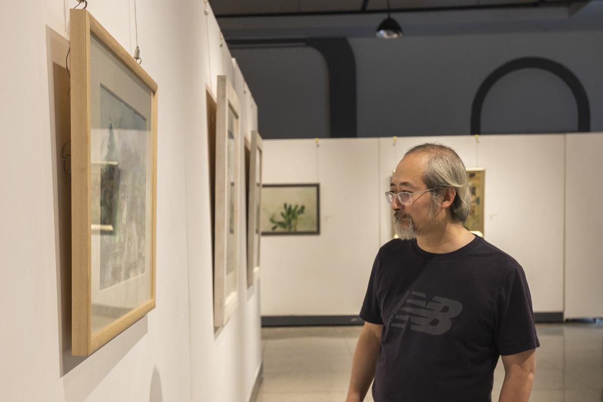 一位校友正在欣赏于艺术馆举行的新中国成立70周年武汉变迁学生美术作品展【学通社记者 章洁瑜 摄】