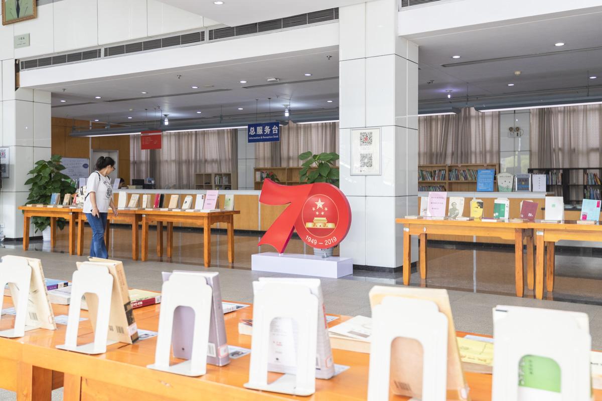 """一位同学正在参观图书馆二楼大厅举行的""""70年:影响中国人精神成长的文学作品展"""" 【学通社记者 章洁瑜 摄】"""