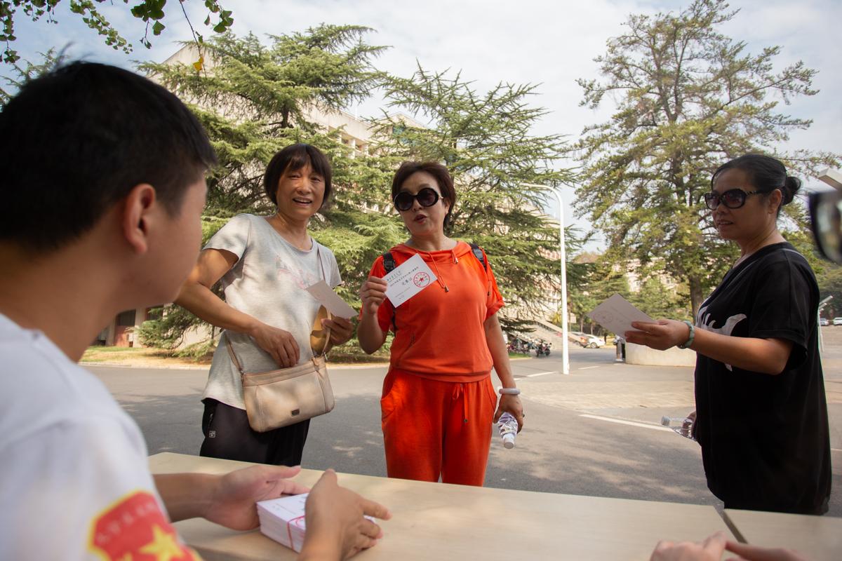 参赛校友与发放完赛证的学生交流【学通社记者 陈赞摄】