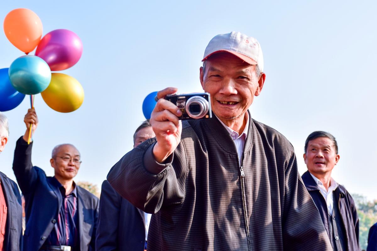 14 队列拿着相机拍照的老人【学通社记者 于君摄】