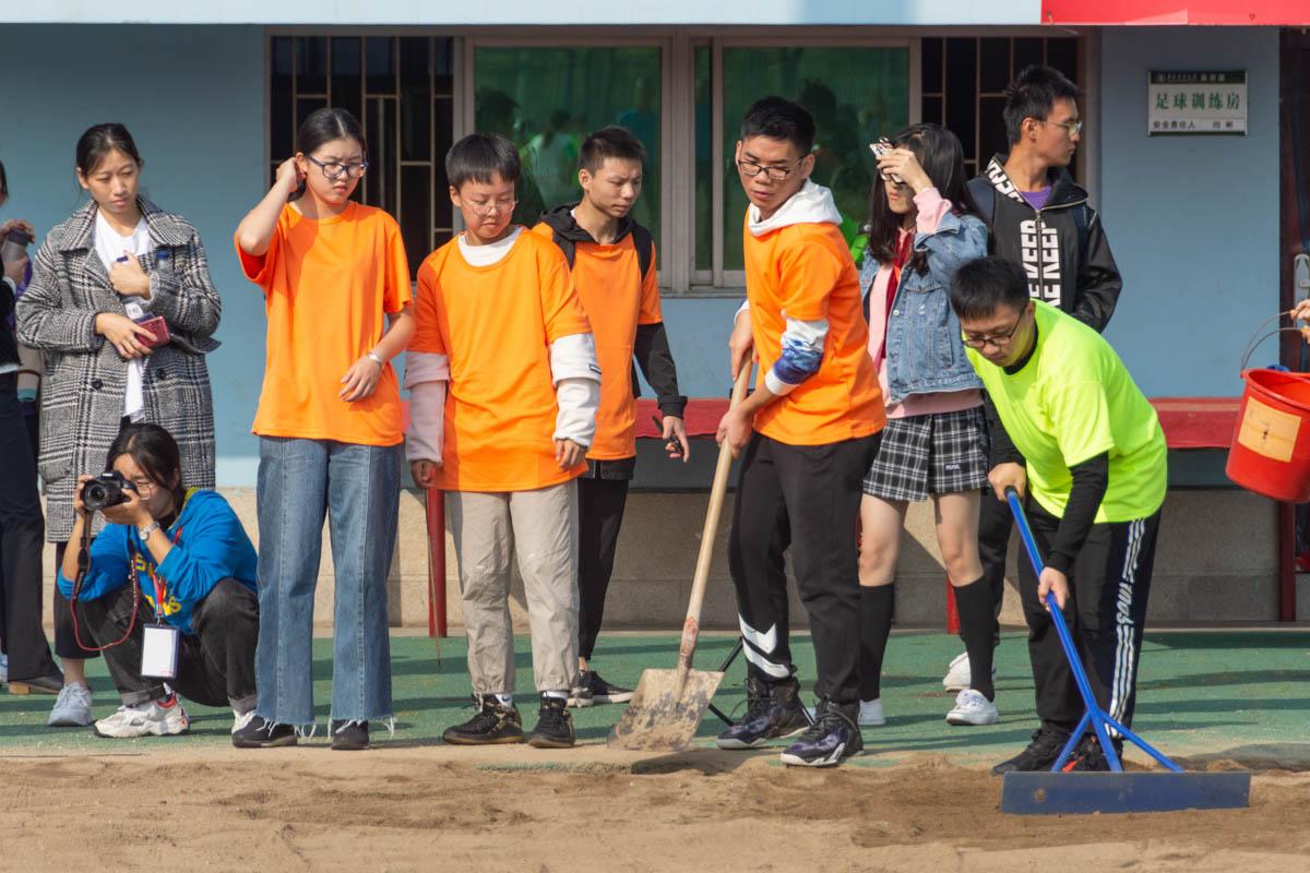 志愿者们正在填平沙坑(学通社记者 万思邑 摄)