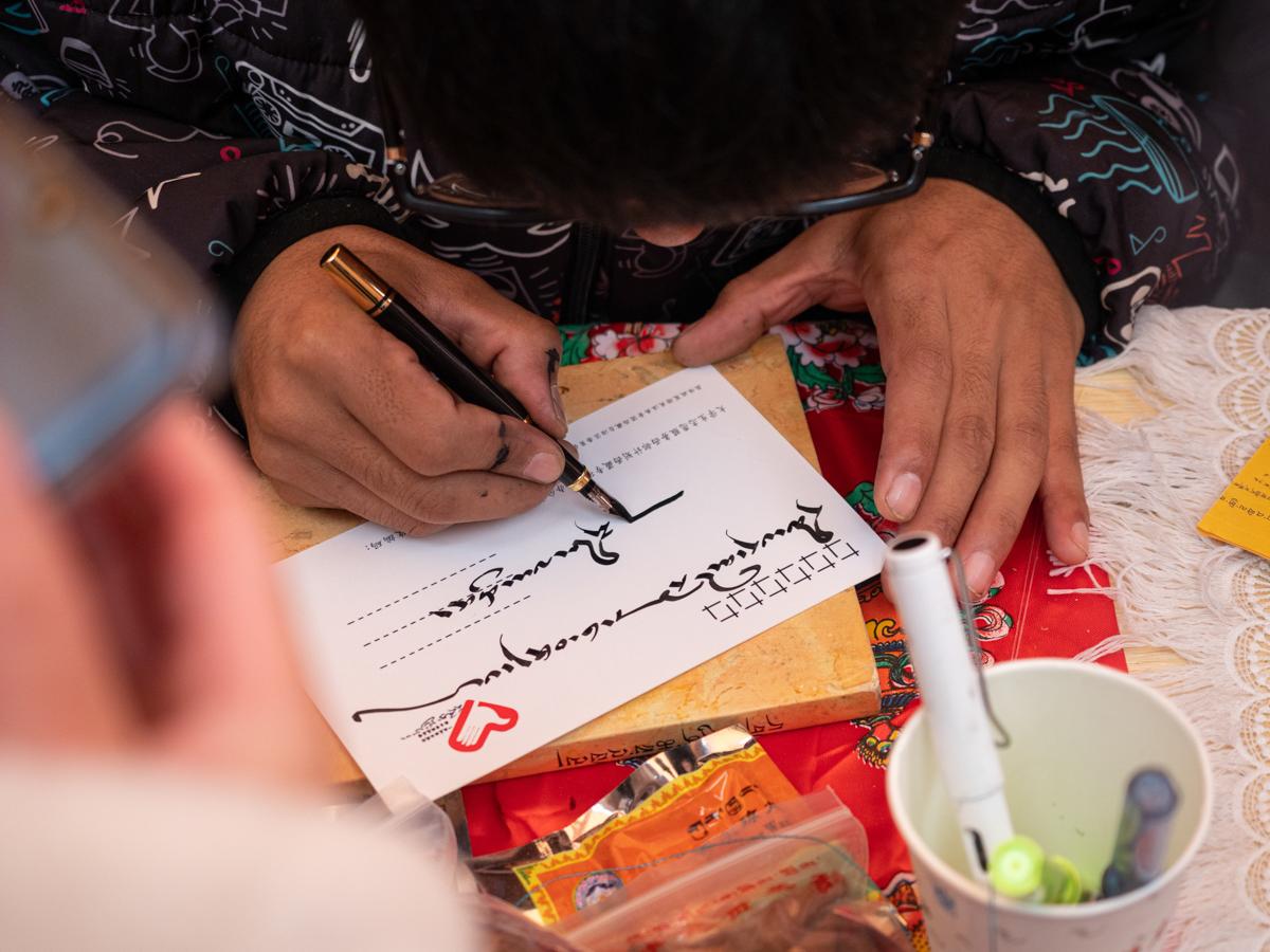 藏族同学正为看展同学用藏文写明信片【学通社记者 包丞 摄】