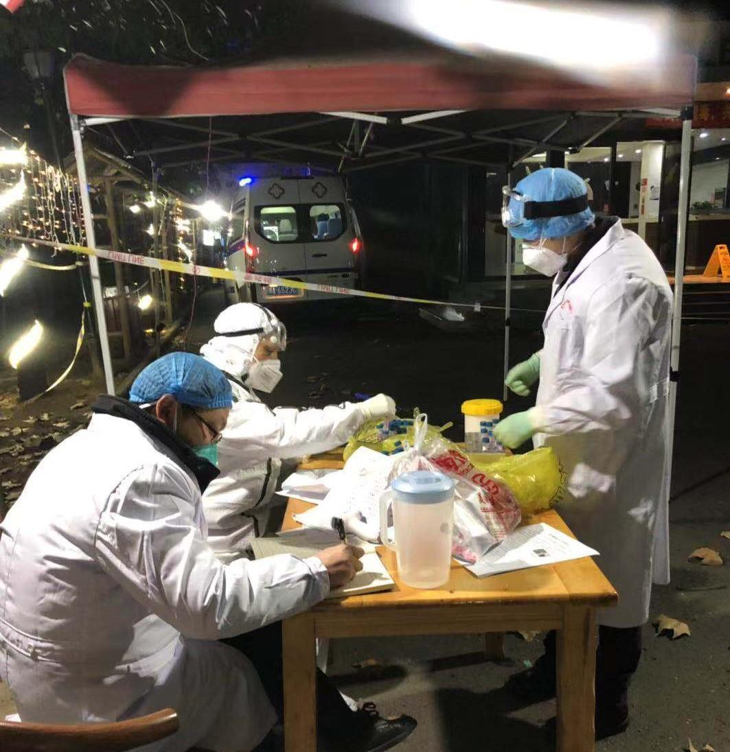 2月4日凌晨,医护人员在在洪山区隔离点门口登记病患信息