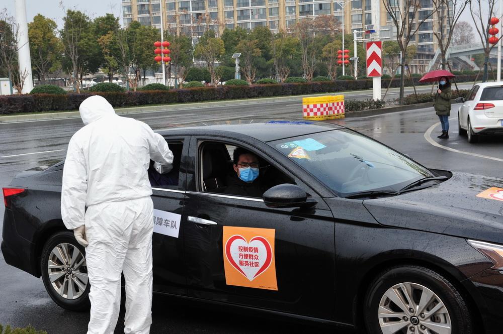 13工作人员对入校车辆人员检测体温