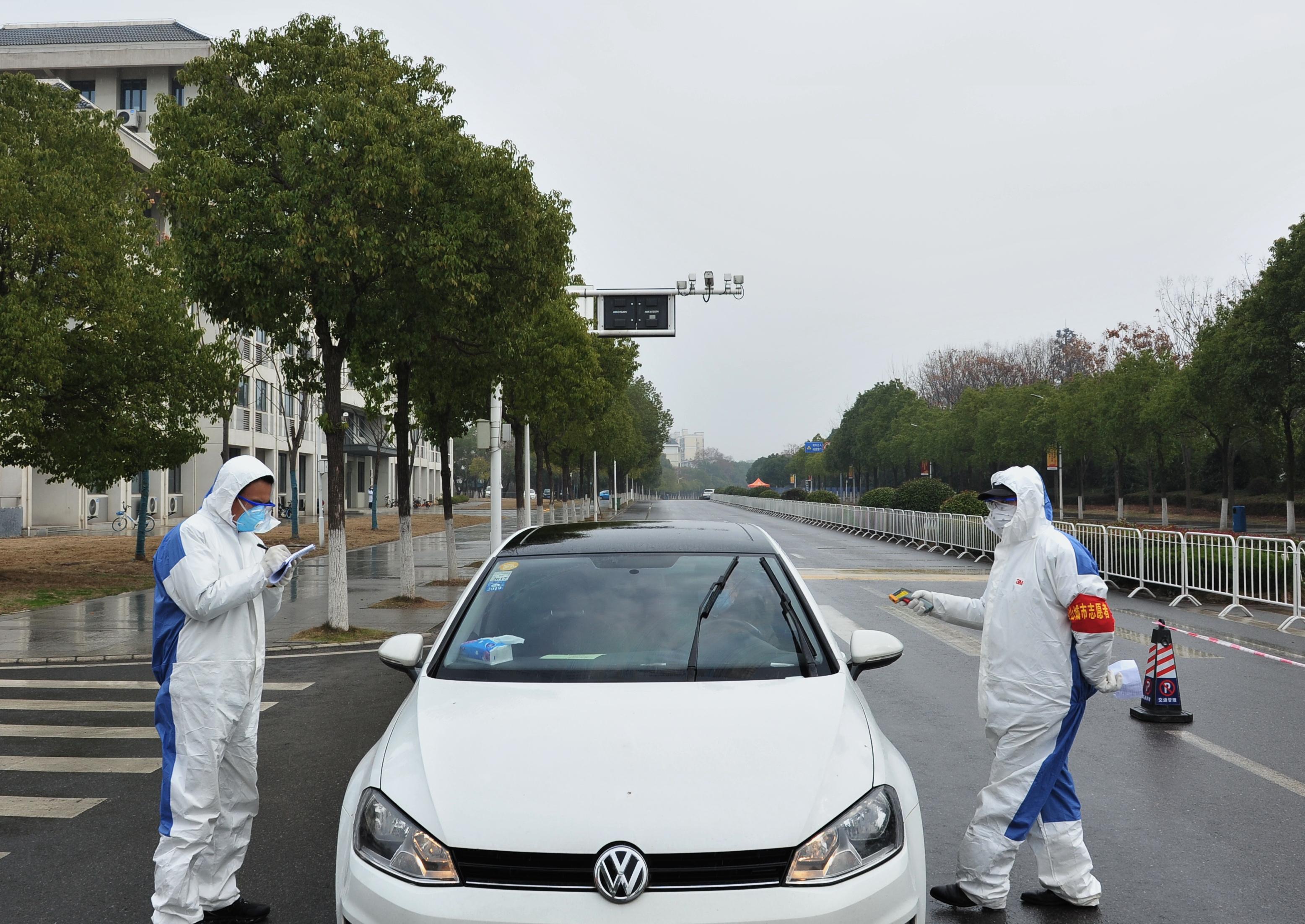 11工作人员对出校车辆进行体温检测和信息登记1