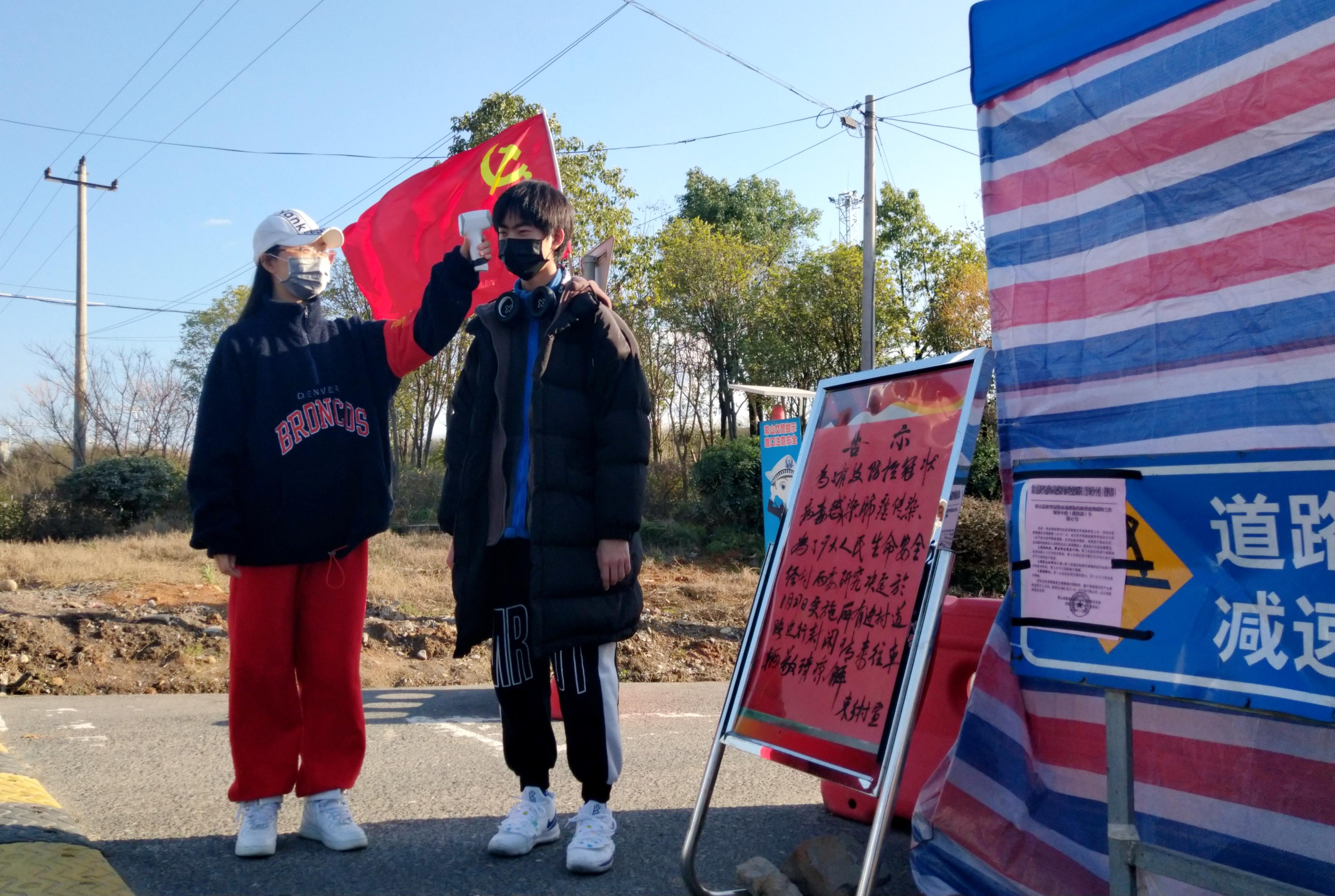 5 文管张之洞班党支部陈丹青在村口给居民测量体温