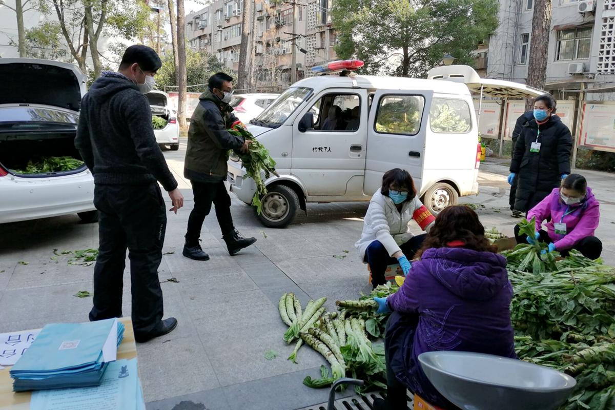 2.2肖万斌(左二)和社区工作人员一起整理分发蔬菜