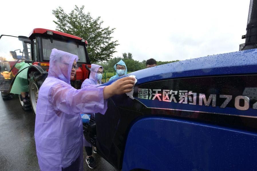 工学院毕业生擦拭拖拉机(刘涛 摄)