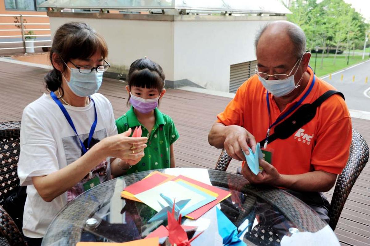 楼管林晓晶、程美珍夫妇和孙女一起折纸鹤(徐行 摄)