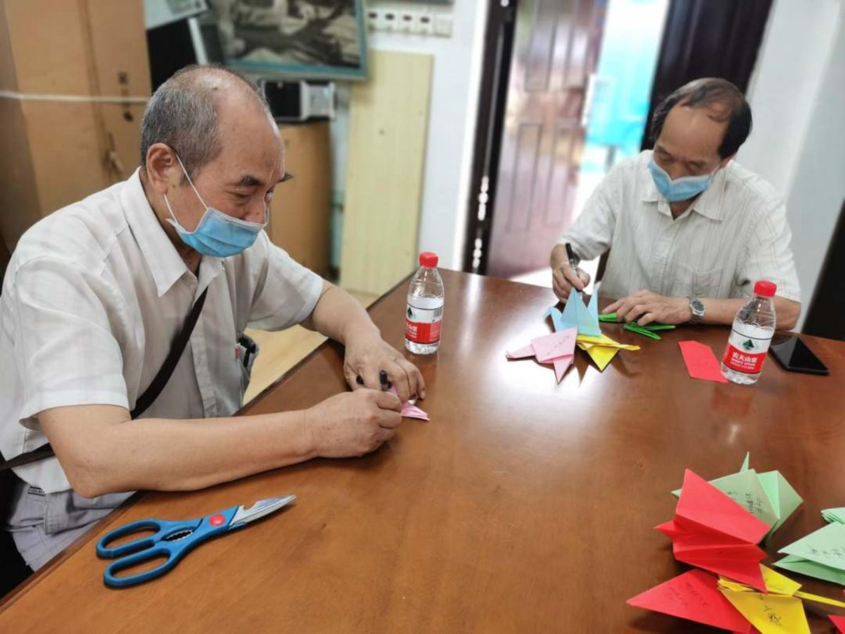 植科院退休教师在离退休活动中心为毕业生折纸鹤(龙健飞 供图)
