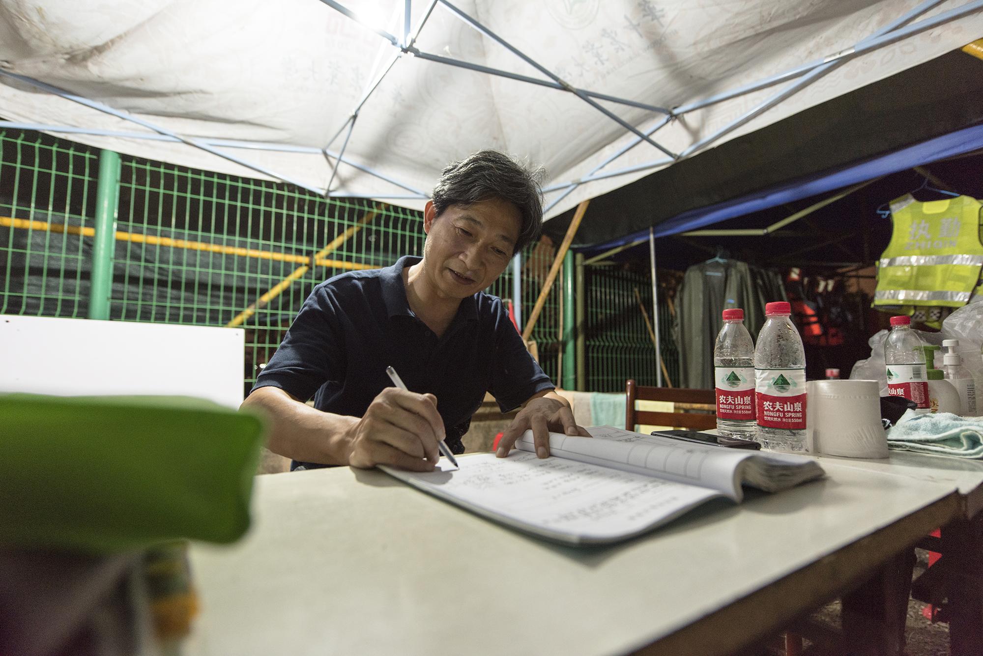 校党委书记高翅检查巡防日志并在日志上签字(记者 刘涛 摄)
