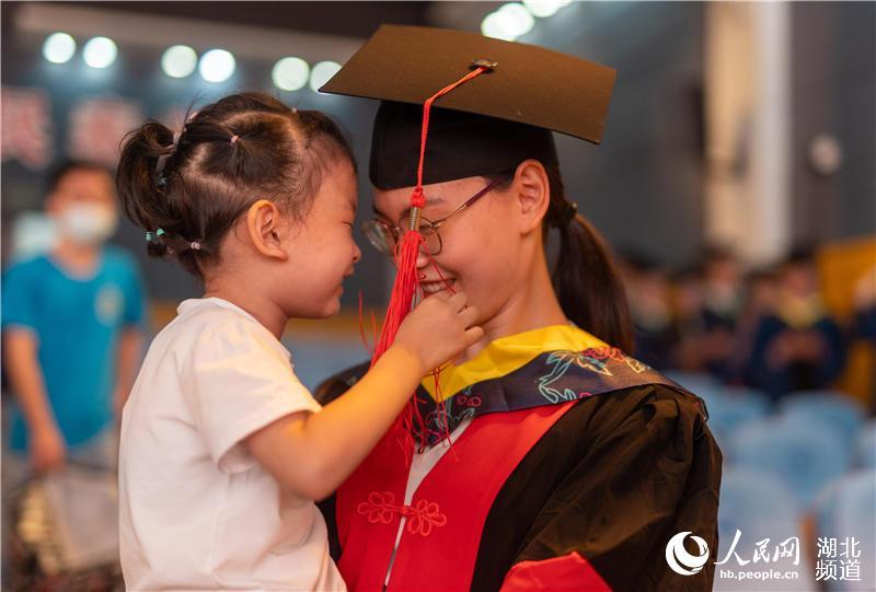 毕业学子与孩子一同参加典礼(刘博文 摄)