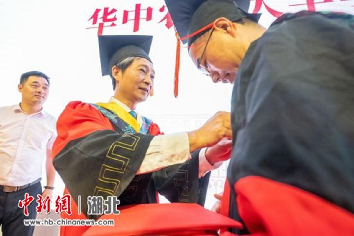 <p>校党委书记高翅为学生整理学位服 刘博文 摄</p>