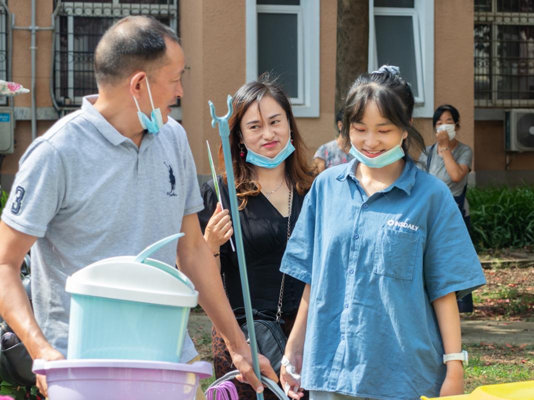 购置完宿舍用品后,新生和父母说笑着走向宿舍(学通社记者 周丹丹 摄)