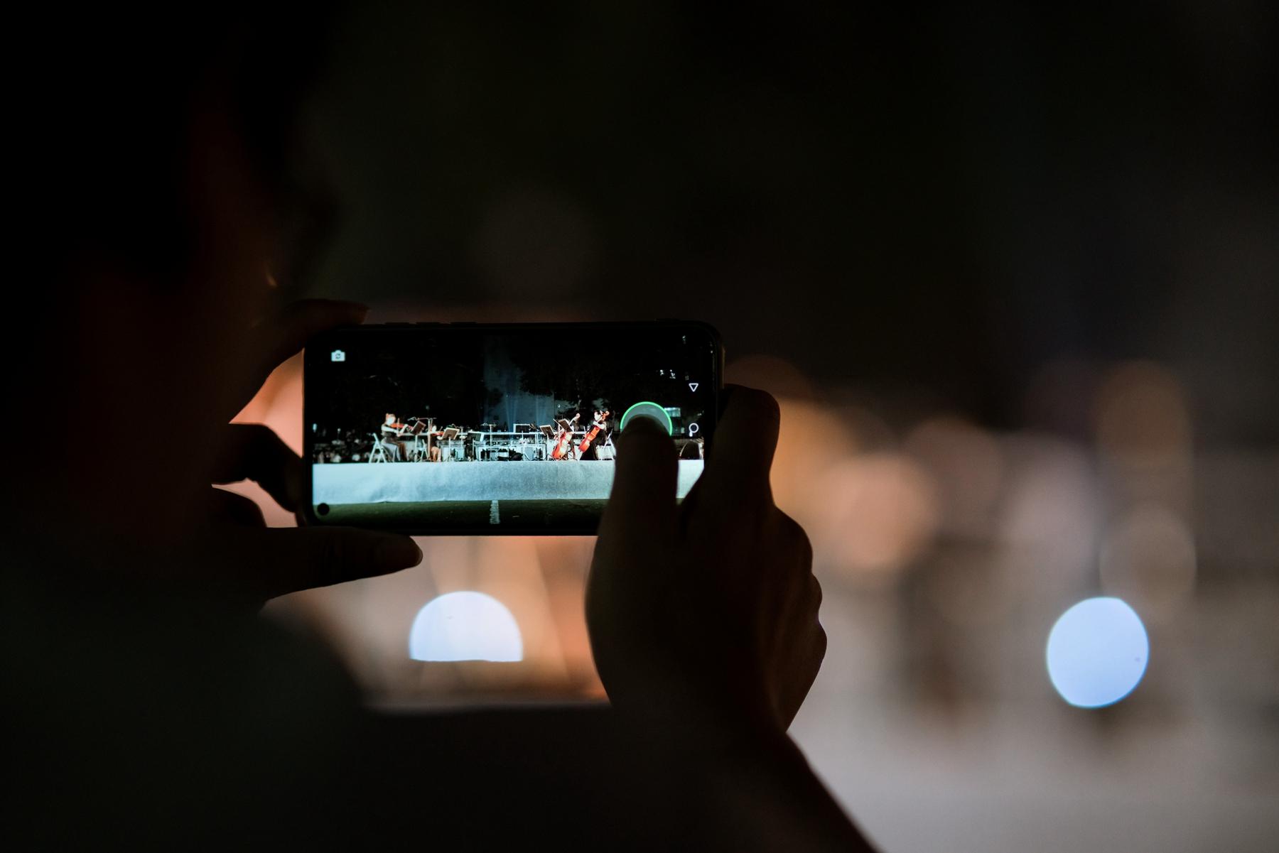 正在用手机记录表演的不雅观众【学通社记者 张晨夕 摄】