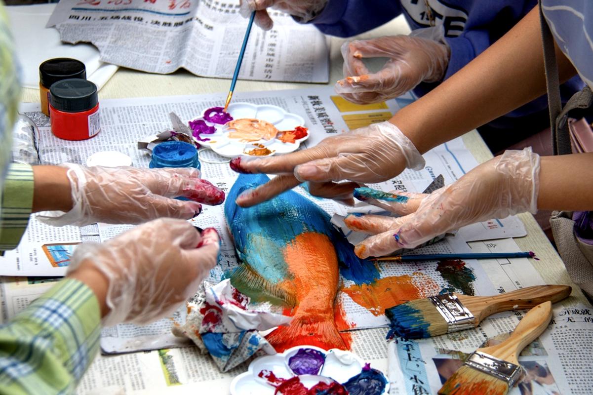 体验者正在用手将颜料涂匀【学通社记者 孙嘉豪 摄】_副本