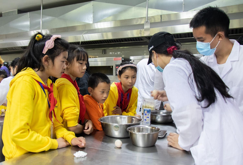 志愿者为小伴侣展示如何打鸡蛋(学通社记者 邵子衿 摄)