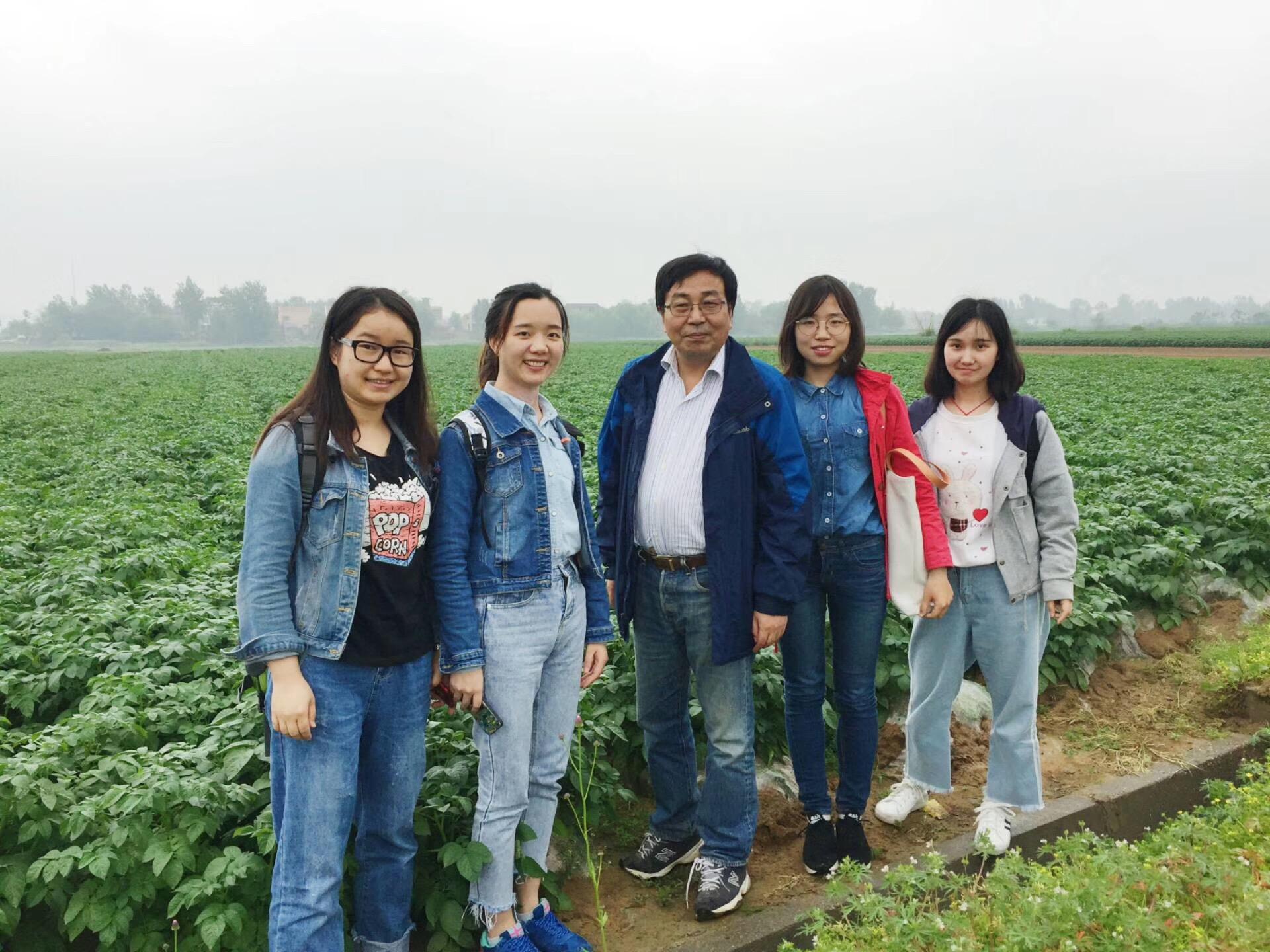 钟老师和学生们在田间调研时合影