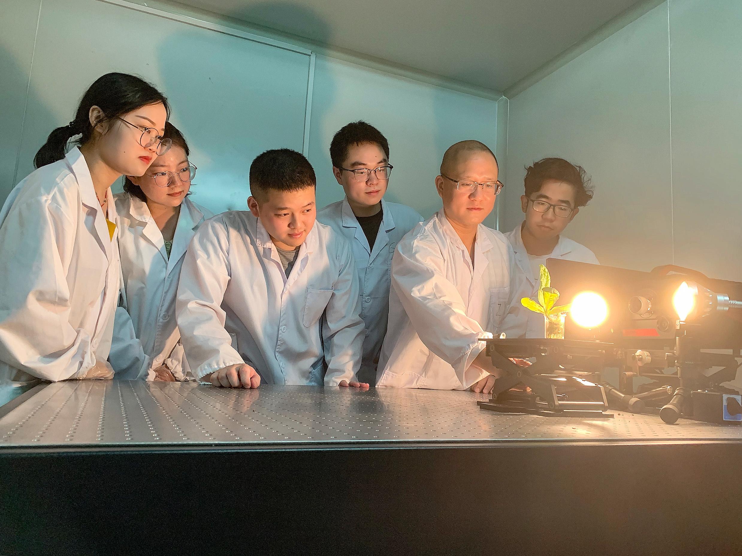 理学院谭佐军老师在实验室指导研究生