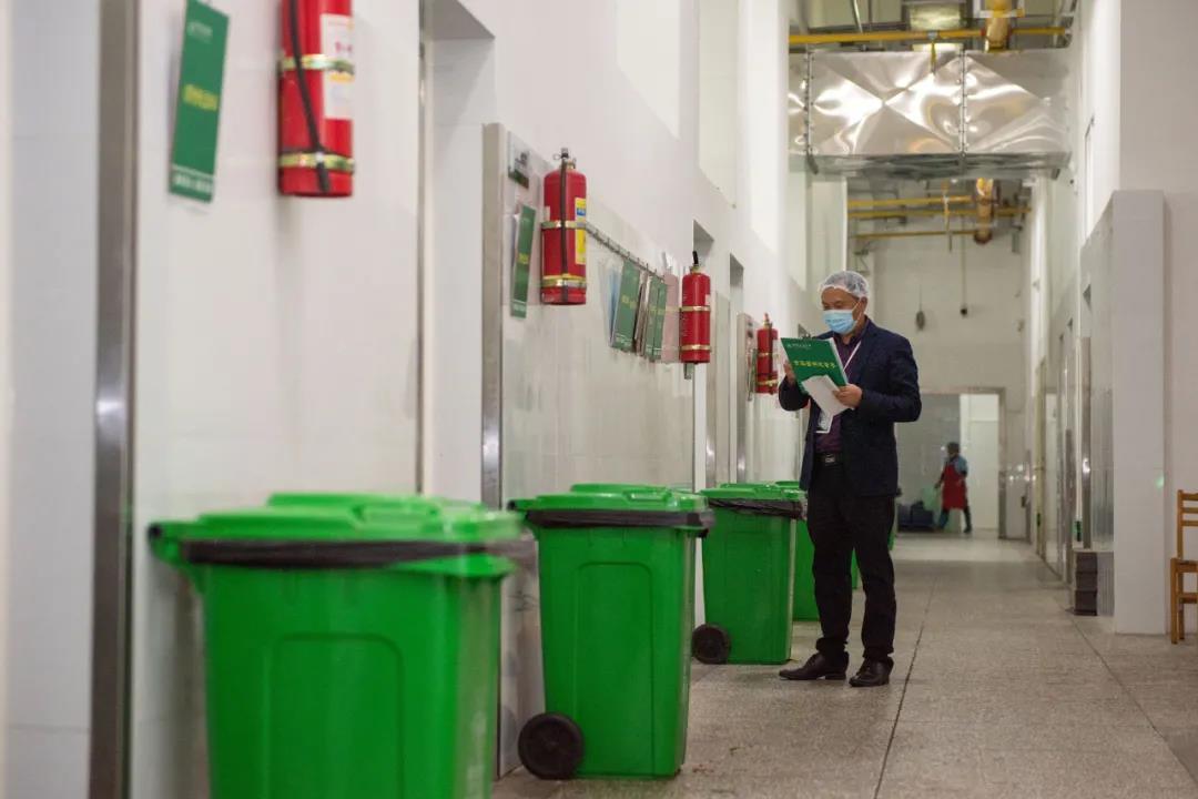 饮食办事中心工作人员按期检查《食品留样记录本》的记录情况(段智为 摄)