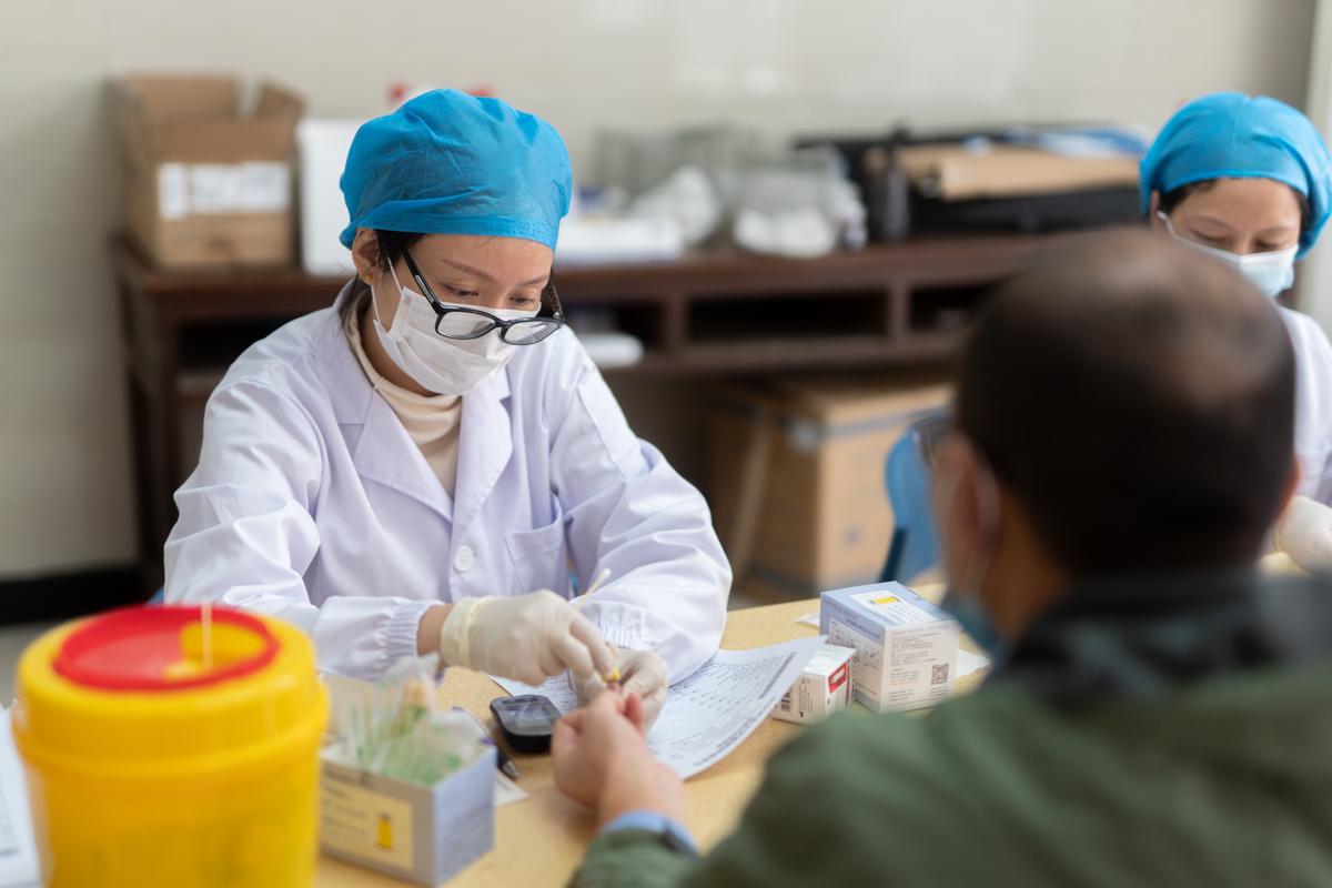 医护人员正在为教职工测量血糖(学通社记者 刘博文 摄)
